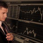 株チャートを見つめる投資家男性